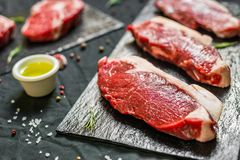 Beef cow meat steaks with spices and herbs against black background. Beef meat steaks with spices and herbs against black background stock photos