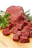 Beef cubes. Raw fresh beef cubes on board with greens Stock Photos