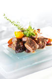 Beef cubes. With raisins tomato and herbs on a glass plate Royalty Free Stock Photography