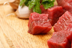 Beef cubes. Raw fresh beef cubes on board with greens Royalty Free Stock Photo