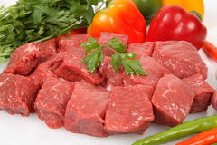 Beef cubes. With vegetable background Royalty Free Stock Photo