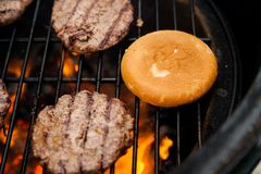 Beef cutlet on grill with bun Stock Image