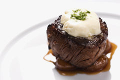 Beef Dinner Entree. Beef filet dinner entree with garnish and brown sauce displayed on a white dinner plate. Horizontal shot Stock Image