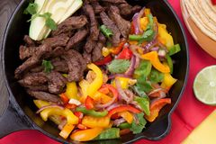 Beef Fajitas In Cast Iron Skillet. Beef fajitas with bell pepper, onion, and avocado in cast iron skillet ready to be served Royalty Free Stock Photos