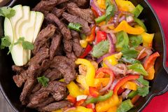 Beef Fajitas In Cast Iron Skillet. Beef fajitas with bell pepper, onion, and avocado in cast iron skillet ready to be served Royalty Free Stock Photography