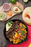 Beef Fajitas In Cast Iron Skillet. Beef fajitas with bell pepper, onion, and avocado in cast iron skillet ready to be served Royalty Free Stock Photo
