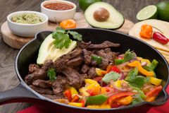 Beef Fajitas In Cast Iron Skillet. Beef fajitas with bell pepper, onion, and avocado in cast iron skillet ready to be served Stock Images