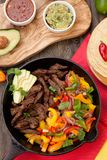 Beef Fajitas In Cast Iron Skillet. Beef fajitas with bell pepper, onion, and avocado in cast iron skillet ready to be served Stock Photo
