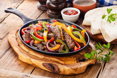 Beef Fajitas. With colorful bell peppers in pan and tortilla bread and sauces Stock Photo