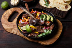 Beef fajitas. Beef fajita with bell peppers. Tortillas, avocado, sauce served with grilled beef and vegetables on skillet. Tex-mex cuisine Stock Images