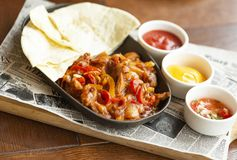 Beef Fajitas with onions and colored pepper, served with tortillas, cheese sauce, salsa and sour cream. Traditional dish of Mexico. Beef Fajitas with onions and royalty free stock photo