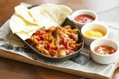 Beef Fajitas with onions and colored pepper, served with tortillas, cheese sauce, salsa and sour cream. Traditional dish of Mexico. Beef Fajitas with onions and stock images