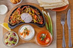 Beef Fajitas. Veal, onion, pepper, jalapeno pepper, lavash, avocado, sour cream and spicy bean sauce stock image