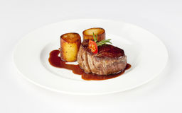 Beef filet. With fondant potato and red wine sauce on a white plate royalty free stock image