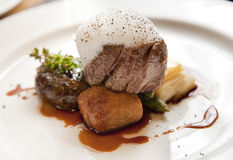 Beef fillet. Roasted bone marrow, oxtail rilette,roasted potato gratin,sauted asaparagus,truffle foam and beef jus on a white plate as a main course Stock Image