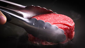 Beef fillet is put into the pan with a steel pliers. Stock Photography