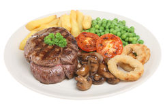 Beef Fillet Steak Dinner. Fillet steak with chips, mushrooms, peas and onion rings Royalty Free Stock Photos