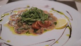Beef or fish carpaccio with parmesan, lemon and arugula in modern restaurant, top view stock video