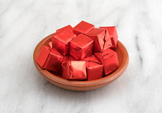 Beef flavored bouillon cubes wrapped in a small bowl. Several beef flavored bouillon cubes in red tinfoil wrappers filling a small dish atop a gray marble Royalty Free Stock Photos