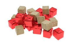 Beef flavored bouillon cubes wrapped and unwrapped. Several beef flavored bouillon cubes in red tinfoil wrappers plus unwrapped ready to use isolated on a white Stock Photo