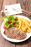 Beef and french fries. On wood Royalty Free Stock Images