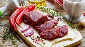 Beef. Fresh raw meat on a cutting Board, olive oil, garlic, hot pepper, thyme and spices Royalty Free Stock Image