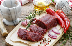 Beef. Fresh raw meat on a cutting Board, olive oil, garlic, hot pepper, thyme and spices Stock Photos