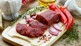 Beef. Fresh raw meat on a cutting Board, olive oil, garlic, hot pepper, thyme and spices Royalty Free Stock Photos
