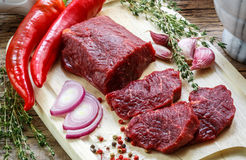 Beef. Fresh raw meat on a cutting Board, olive oil, garlic, hot pepper, thyme and spices Stock Photography
