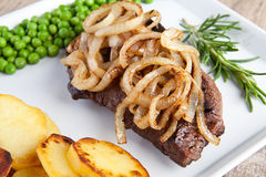 Beef with fried potatoes and green peas Stock Photos