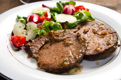 Beef  garnished with fresh salad Royalty Free Stock Photo