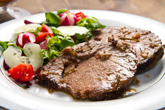 Beef  garnished with fresh salad Royalty Free Stock Image