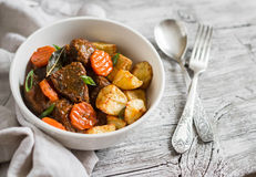 Beef goulash with carrots and roasted potatoes in a white bowl Royalty Free Stock Photo
