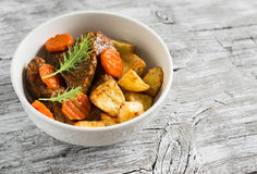 Beef goulash with carrots and roasted potatoes in a white bowl Royalty Free Stock Image