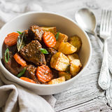 Beef goulash with carrots and roasted potatoes in a white bowl Stock Photo