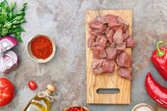 Beef for goulash and ingredients. Meat cubes on an old wooden chopping board and ingredients for cooking on rustic background Royalty Free Stock Photos