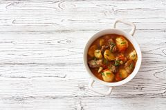 Beef Goulash with Potatoes, Carrots and Mushrooms. Beef Goulash with Potatoes, Carrots , Mushrooms and Seasoning on White Wood Background. Top view with Copy royalty free stock images