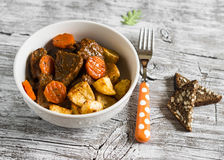 Beef goulash and roasted potatoes in a white bowl Stock Photos