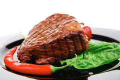 Beef grilled and garnished with green lettuce and red chili hot Stock Images