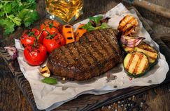 Beef grilled steak with grilled vegetables and glass of whiskey Stock Photos