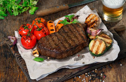 Beef grilled steak with grilled vegetables and lager beer. Close up beef grilled steak with set of grilled vegetables and lager beer on wooden table Royalty Free Stock Images