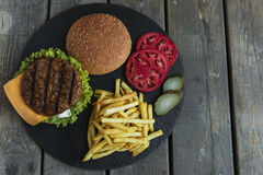 Beef hamburger grill french fries pickled cucumber tomato cheese stock photography