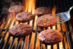Beef hamburger patties sizzling on the barbecue Stock Photo