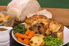 Beef in Irish Stout Pie. A Beef in Irish Stout Pie with Pan Haggerty potato with Stout battered onion rings and Sourdough Bread Stock Images