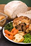 Beef in Irish Stout Pie. A Beef in Irish Stout Pie with Pan Haggerty potato with Stout battered onion rings and Sourdough Bread Royalty Free Stock Photo