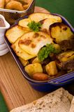 Beef in Irish Stout Stew. A dish of Beef in Irish stout with a topping of sliced potatoes, served with a selection of vegetables and Sourdough bread, with stout Royalty Free Stock Images
