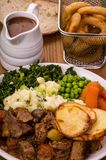 Beef in Irish Stout Stew. A dish of Beef in Irish stout with a topping of sliced potatoes, served with a selection of vegetables and Sourdough bread, with stout Royalty Free Stock Photo