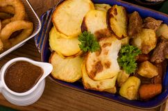 Beef in Irish Stout Stew. A dish of Beef in Irish stout with a topping of sliced potatoes, served with a selection of vegetables and Sourdough bread, with stout Stock Photos