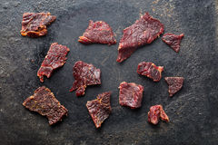 Beef jerky on old black table Stock Photography