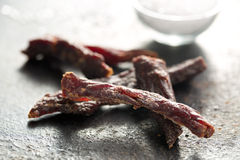 Beef jerky. On old table Royalty Free Stock Image